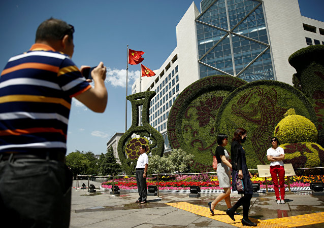 A man takes pictures of a flower display set up ahead of the Belt and Road Forum in central Beijing, China, May 10, 2017