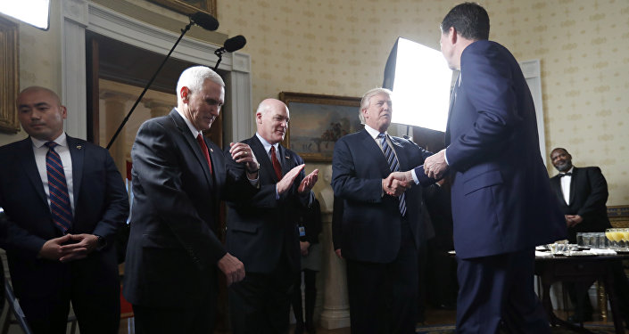 Vice President Mike Pence, second from left, and Secret Service Director Joseph Clancy stand as President Donald Trump shakes hands with FBI Director James Comey during a reception for inaugural law enforcement officers and first responders in the Blue Room of the White House, Sunday, Jan. 22, 2017 in Washington