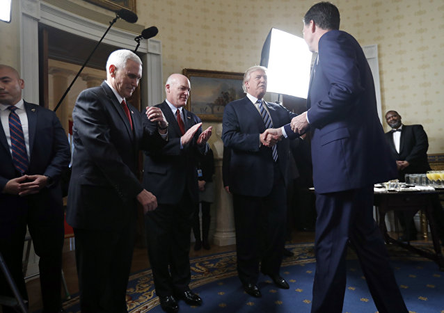 Vice President Mike Pence, second from left, and Secret Service Director Joseph Clancy stand as President Donald Trump shakes hands with FBI Director James Comey during a reception for inaugural law enforcement officers and first responders in the Blue Room of the White House, 22 January 2017 in Washington