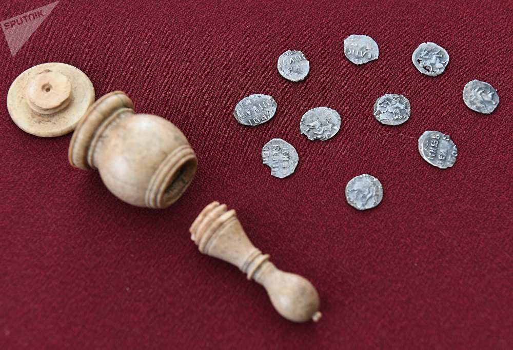 Hand minted silver coins from the time of Ivan the Terrible (16th century) that were found inside an ivory chess bishop figure shown as part of a display of archeological finds discovered in Prechistenka Street as it was being renovated under the My Street programme in Moscow
