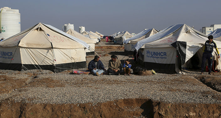 Displaced Iraqis, who fled fighting between Iraqi security forces and Islamic State militants, sit at the Hassan Sham camp, east of Mosul, Iraq, Monday, Jan. 23, 2017