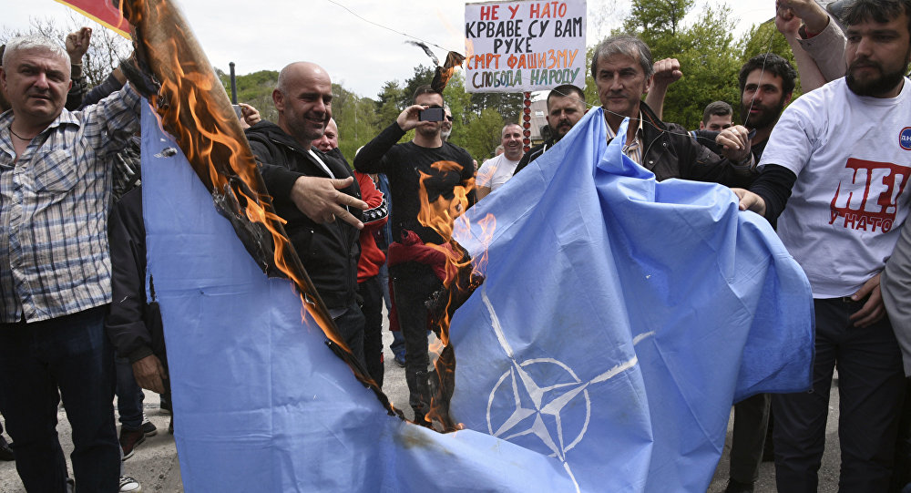 Anti-NATO demonstrators burn a NATO flag in front of a a banner that reads: No to NATO, your hands are bloody - Death to fascism, freedom to the people, during a protest outside the hall before the parliament session in Cetinje, Montenegro, Friday, April 28, 2017