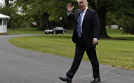 Trump waves as he walks into the White House in Washington