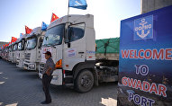 A Chinese worker stands near trucks carrying goods during the opening of a trade project in Gwadar port, some 700 kms west of the Pakistani city of Karachi on November 13, 2016.