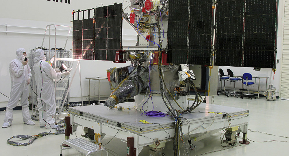 In this Nov. 24, 2014 photo made available by NASA, workers conduct a light test on the solar arrays on NOAA's Deep Space Climate Observatory spacecraft (DSCOVR) in Titusville, Fla., near Kennedy Space Center.