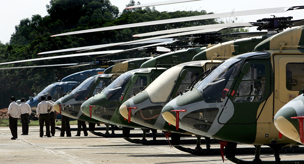 Officials walk past a line of parked Dhruv helicopters of India's Hindustan Aeronautics Ltd. (HAL) standing on the tarmac at The HAL helicopter division in Bangalore