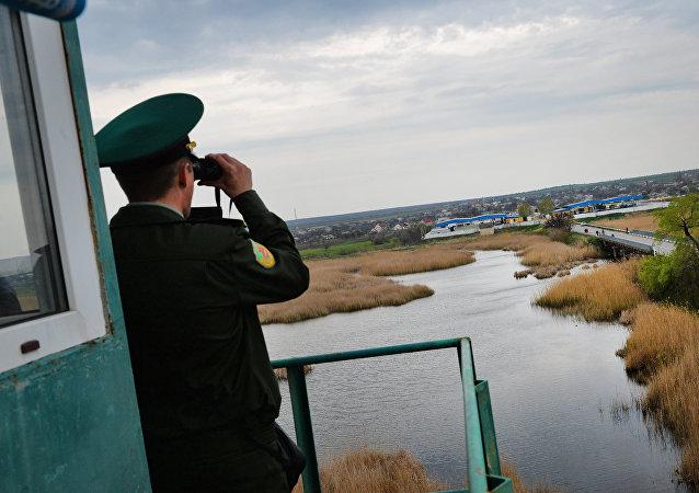 A transdniestr border police officer from separatist region of Moldova looks at Ukraine border point at Kuchurgan-Pervomaysk, Ukraine-Moldova border point on April 15, 2014.