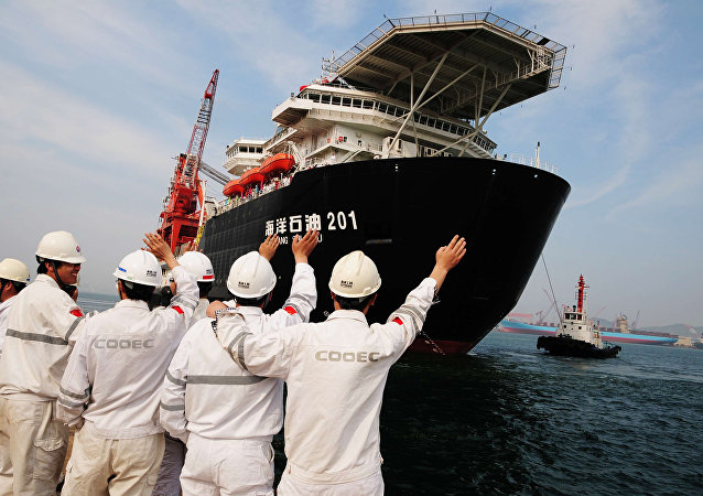 Chinese port workers wave as China National Offshore Oil Corp. (CNOOC)'s first independent deep-water oil drilling rig, was sent off from the port of Qingdao, east China's Shandong province. China's first home-grown deep-water drilling rig will be located in the South China Sea, some 300 kilometres (200 miles) southeast of Hong Kong