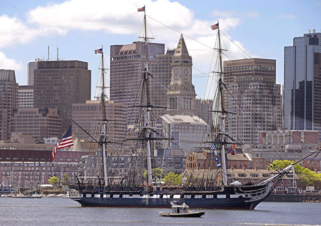 The USS Constitution, or Old Ironsides, the US Navy's oldest commissioned ship is towed through Boston Harbor past the financial district skyline in honor of the 70th Anniversary of D-Day Friday, June 6, 2014 in Boston.