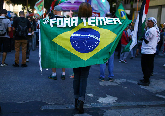 A demonstrator carries a Brazilian national flag as she attends a protest against Brazil's President Michel Temer in Rio de Janeiro, Brazil, May 18, 2017
