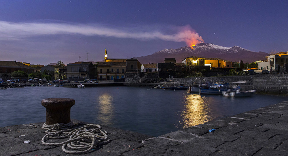 Snow-covered Mount Etna, Europe's most active volcano, spews lava during an eruption as the Sicilian village of Pozzillo, Italy, is visible in foreground, in the early hours of Tuesday, April 11, 2017