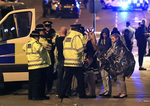 Emergency services personnel speak to people outside Manchester Arena after reports of an explosion at the venue during an Ariana Grande concert in Manchester, England, Monday, May 22, 2017.