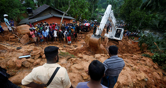 People gather during a rescue mission at the site of a landslide in Bellana village in Kalutara, Sri Lanka May 26, 2017