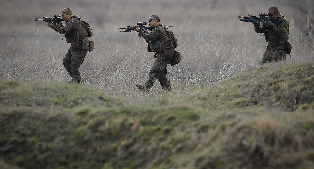US Marines advance on the Black Sea shore during training at the Capu Midia Surface to Air Firing Range, on the Black Sea coast in Romania