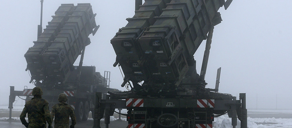 Two soldiers run toward Patriot antimissile systems. File photo