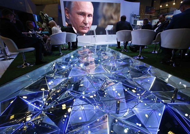 Participants of the St. Petersburg International Economic Forum (SPIEF) sit near an electronic screen showing Russian President Vladimir Putin, who attends a session of the forum in St. Petersburg, Russia, June 2, 2017