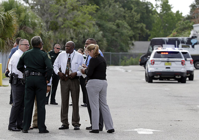 Authorities confer near the scene of a shooting where they said there were multiple fatalities in an industrial area near Orlando, Fla., Monday, June 5, 2017