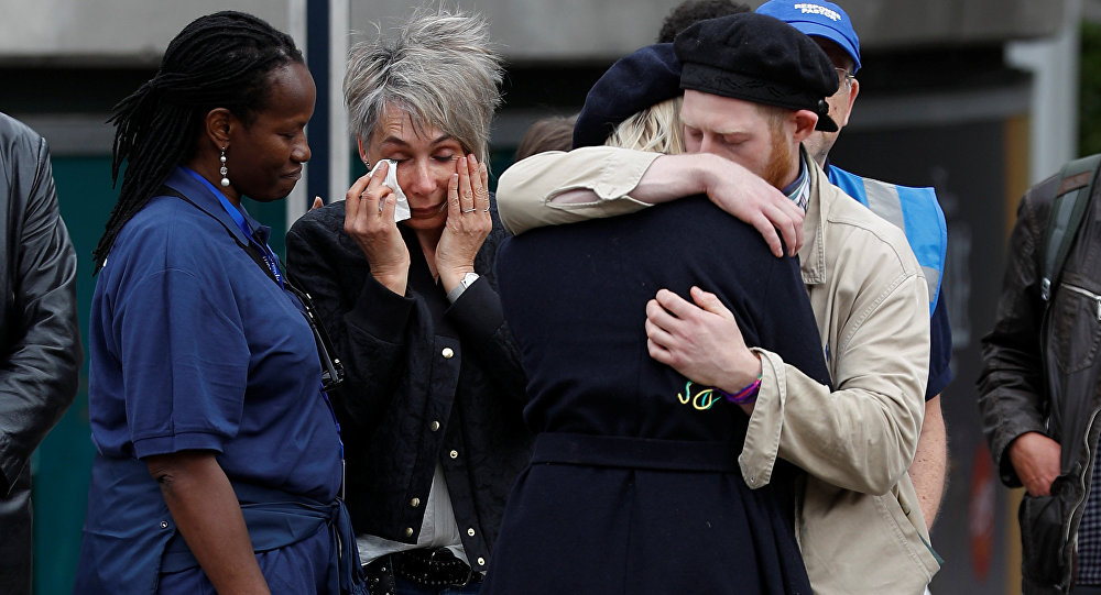 People react in front of floral tributes on the south side of London Bridge near Borough Market after an attack left 7 people dead and dozens of injured in London, Britain, June 5, 2017.