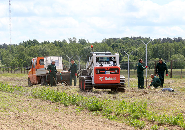 Workers install poles for the fence near the Sudargas border crossing point with Russia in Ramoniskiai, Lithuania June 5, 2017