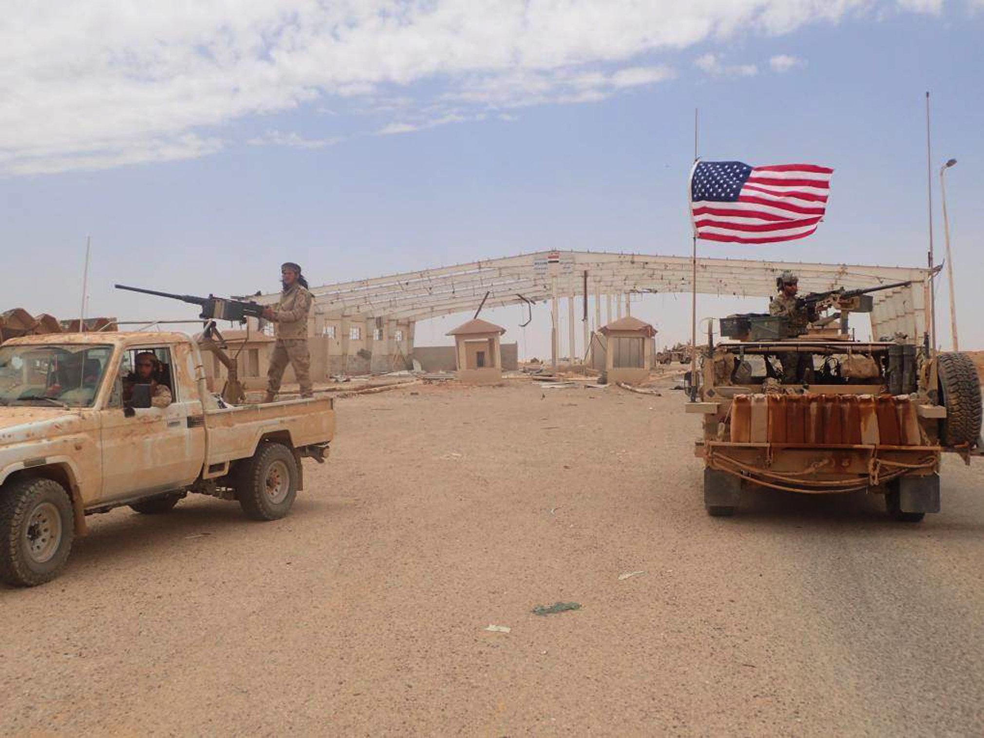 Sur cette photo prise le mardi 23 mai 2017, fournie par le groupe activiste anti-gouvernement syrien, la Justice News de Hammourabi, qui a été authentifiée sur la base de son contenu et d'autres reportages de l'AP, montre une forme de combattant syrien anti-gouvernement Maghaweer al-Thawra se tient sur un véhicule avec une lourde mitraillette automatique, à gauche, à côté d'un soldat américain qui se tient également sur son véhicule blindé, à droite, alors qu'ils prennent position au point de passage syrien-irakien de Tanf.