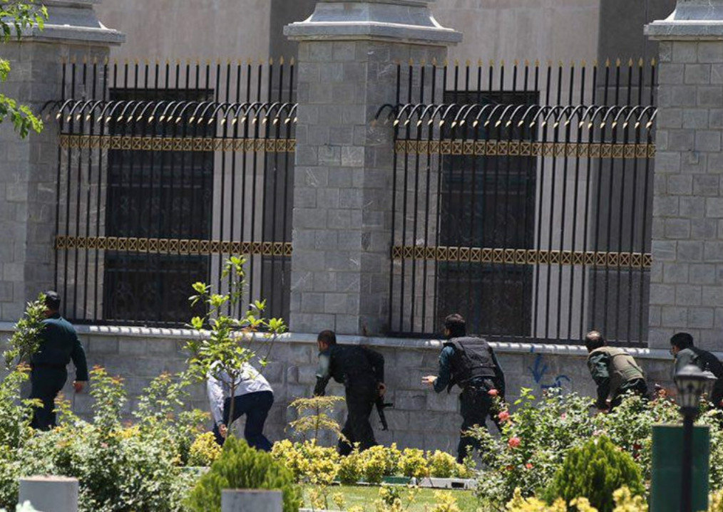 Members of Iranian forces run during an attack on the Iranian parliament in central Tehran, Iran, June 7, 2017