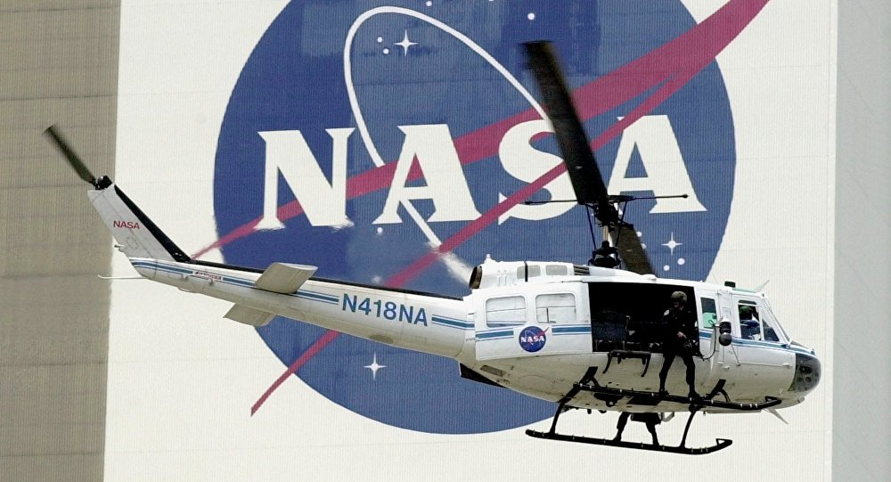 A NASA security helicopter flies by the NASA logo on the Vehicle Assembly Building