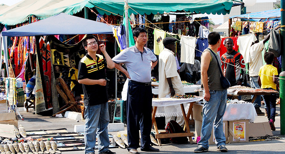 Chinese nationals walk around Arcades Shopping complex's Pakati Market on October 25, 2010 in Lusaka, Zambia