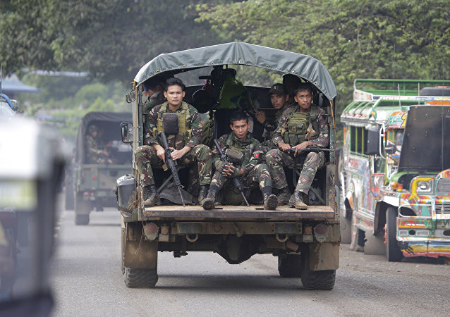 In this June 9, 2017, photo, soldiers ride a military vehicle on the outskirts of Marawi city, southern Philippines. The Philippine military says 13 marines have been killed in fierce fighting with Muslim militants who have laid siege to southern Marawi city.