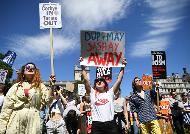 Anti-Conservative Party and anti-Democratic Unionist Party (DUP) demonstrators gather with placards in Parliament Square in front of the Houses of Parliament in central London on June 10, 2017
