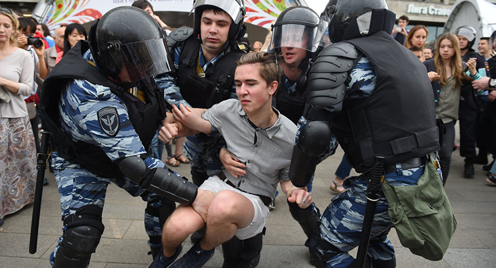 Russian police officers detain a participant of an unauthorized opposition rally in Tverskaya street in central Moscow on June 12, 2017
