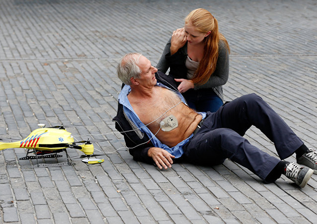 A woman gives a demonstration of an ambulance drone with built in defibrillator at the campus of the Delft Technical University in Delft on October 28, 2014