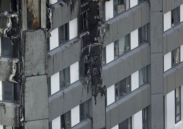 Fire damaged cladding is seen on the lower floors of the fire-gutted Grenfell Tower in London, Friday, June 16, 2017, after a fire engulfed the 24-story building Wednesday morning