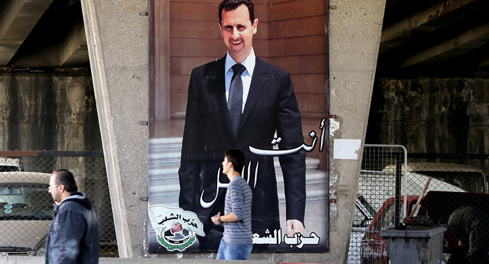 (File) Syrian men walk past a poster bearing a portrait of President Bashar al-Assad in the capital Damascus, on February 27, 2016, as the first major ceasefire of the five-year war takes hold and an international task force prepares to begin monitoring the landmark truce