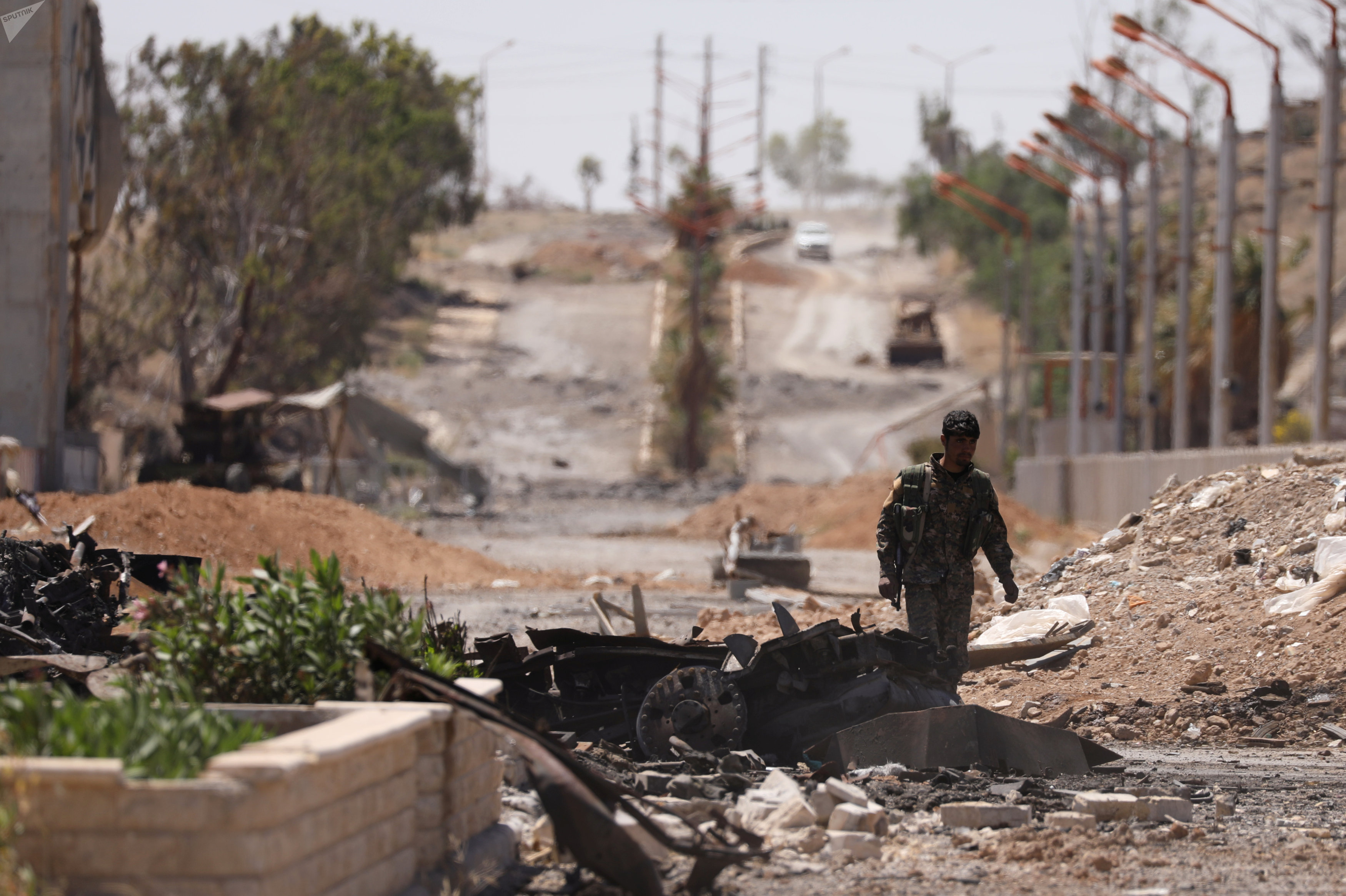 A Syrian Democratic Forces (SDF) fighter walks through a damaged street in the Syrian city of Tabqa, after SDF captured it from Daesh militants, May 12, 2017
