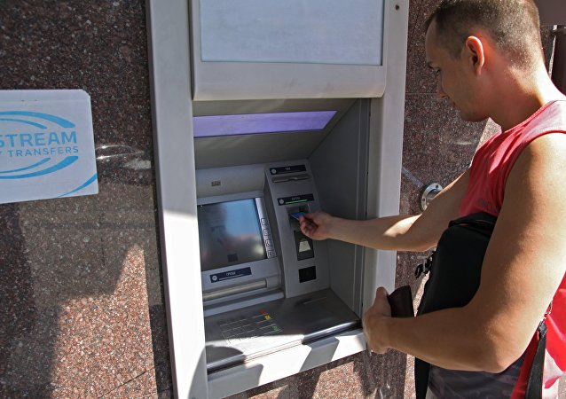 A city resident at a cash dispenser operated by the Central Republican Bank in Donetsk