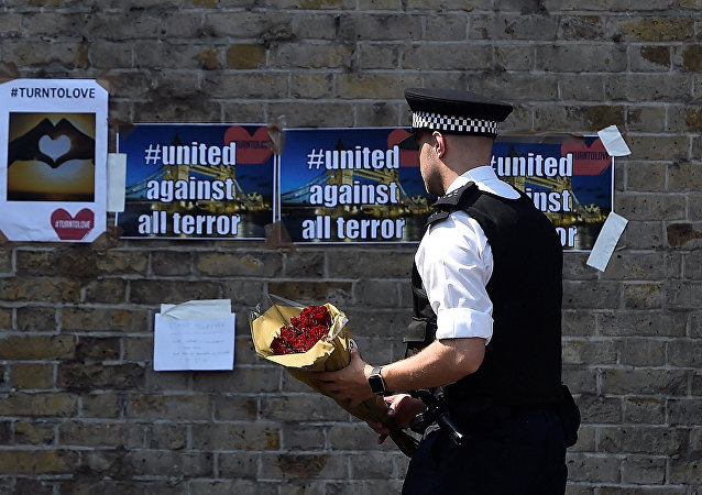 A police officer carries flowers to leave alongside of messages near to where a van was driven at muslims in Finsbury Park, North London, Britain, June 19, 2017