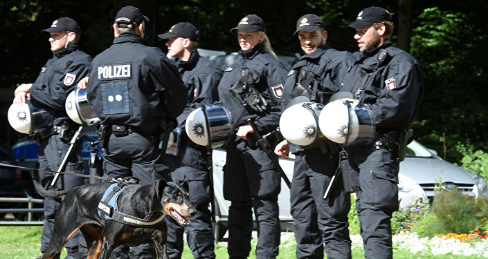 A dog passes a row of police men during a G20 demonstration against the ban of Hamburg's authorities of a G20 protestors camp in the Stadtpark park in Hamburg, Germany June 26, 2017