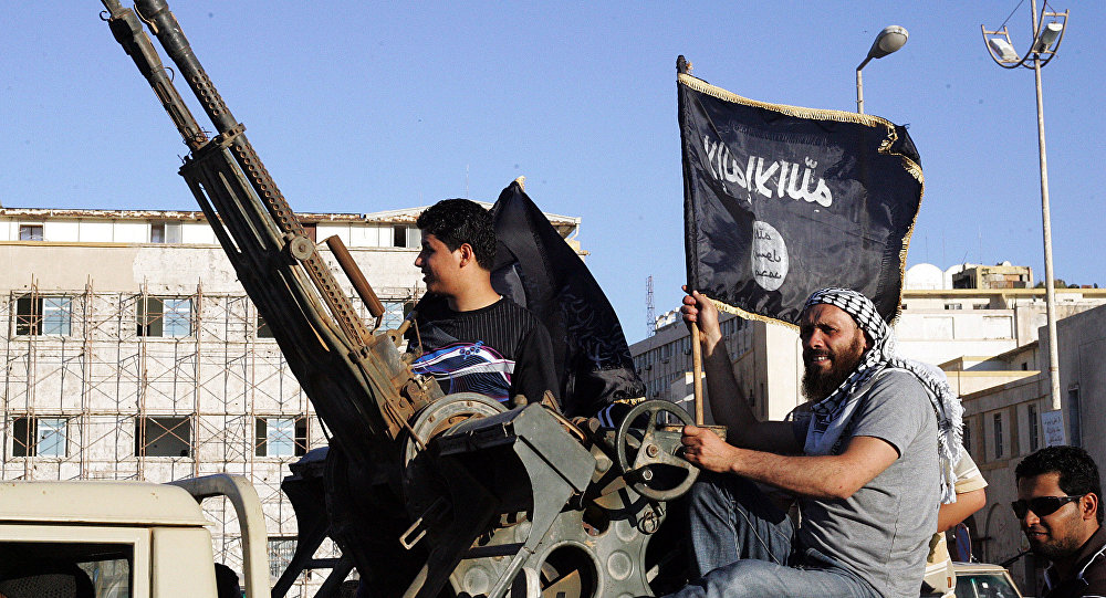 Libyan men hold Al-Qaeda flags while sitting next to an anti-aircraft artillery weapon (File)