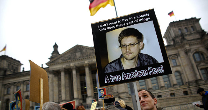 Protesters hold posters of former National Security Agency member Edward Snowden in front of the German parliament building, the Reichstag, prior to a special meeting of the parliament on US-German relationships, in Berlin, Monday, Nov. 18, 2013