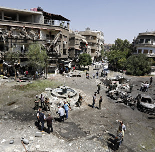 Syrians inspect the site of a suicide bomb attack in the capital Damascus' eastern Tahrir Square district, on July 2, 2017