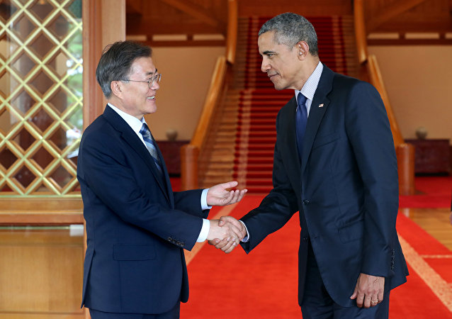 South Korean President Moon Jae-in shakes hands with former U.S. President Barack Obama at the Presidential Blue House in Seoul, South Korea, in this handout picture provided by the Presidential Blue House and released by Yonhap on July 3, 2017