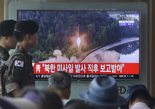 Army soldiers walk by a TV news program showing a file image of a missile being test-launched by North Korea at the Seoul Railway Station in Seoul, South Korea, Tuesday, July 4, 2017.