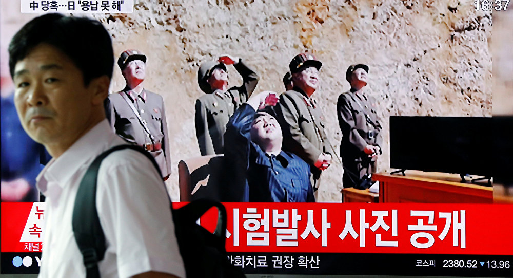A man walks past a TV broadcasting still photographs released by North Korea's state-run television KRT of North Korea's Hwasong-14 missile, a new intercontinental ballistic missile, which they said was successfully tested, at a railway station in Seoul, South Korea, July 4, 2017.