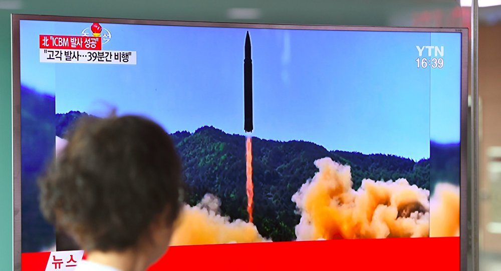 A woman walks past a television screen showing a picture of North Korea's launch of an intercontinental ballistic missile (ICBM), at a railway station in Seoul on July 4, 2017.