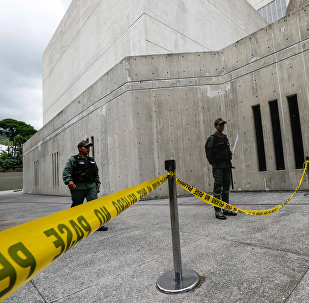 Members of the National Guard stands behind a yellow tape in the area where according to authorities grenades were thrown from a helicopter earlier this week, at the Supreme Court in Caracas on June 29, 2017