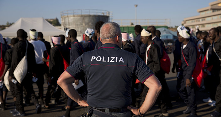 An Italian border police officer escorts sub Saharan men on their way to a relocation center, after arriving in the Golfo Azzurro rescue vessel at the port of Augusta, in Sicily, Italy, with hundreds of migrants aboard, rescued by members of Proactive Open Arms NGO, on Friday, June 23, 2017