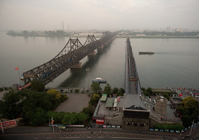 The sun sets over the Friendship bridge on the Yalu River connecting the North Korean town of Sinuiju and Dandong in Chinese border city of Dandong on July 5, 2017