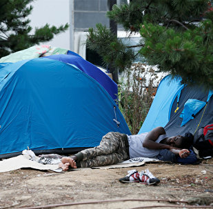 A migrant sleeps next to tents installed in a street near the entrance of the reception center for migrants and refugees at porte de La Chapelle, north of Paris, France, July 6, 2017