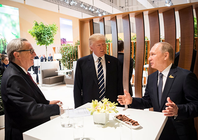 U.S. President Donald Trump, Russia's President Vladimir Putin and President of the European Commission Jean-Claude Juncker talk during the G20 Summit in Hamburg, Germany in this still image taken from video, July 7, 2017