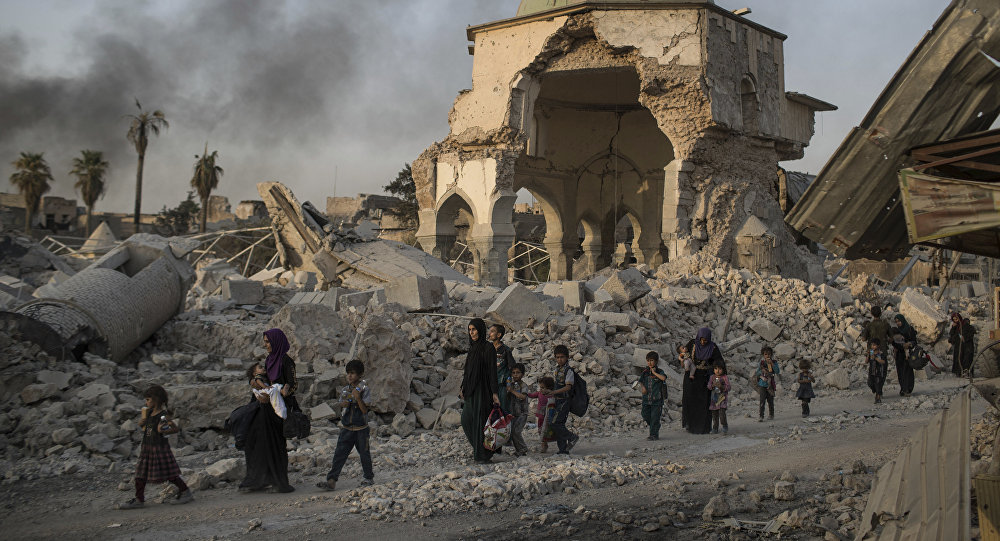 Fleeing Iraqi civilians walk past the heavily damaged al-Nuri mosque as Iraqi forces continue their advance against Islamic State militants in the Old City of Mosul, Iraq, Tuesday, July 4, 2017